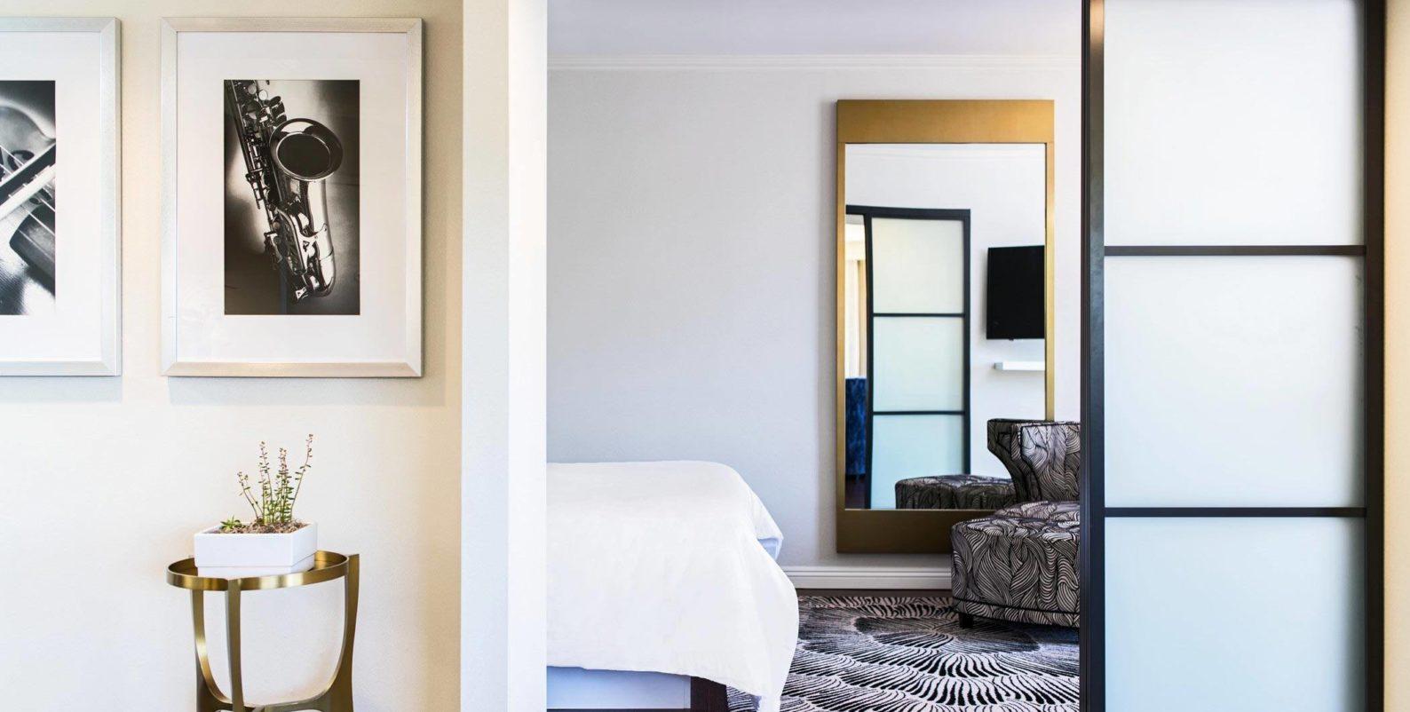 white bed linen near white wooden framed glass door