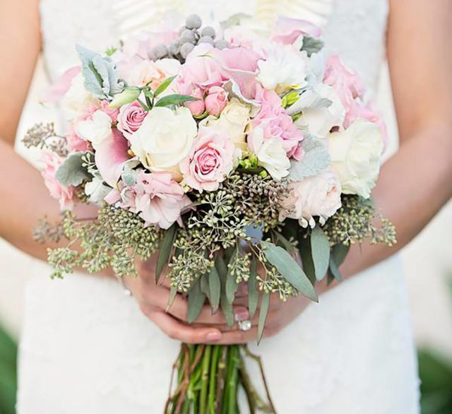woman in white wedding dress holding bouquet of white and pink roses