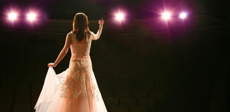 women's orange sleeveless dress singing on a stage
