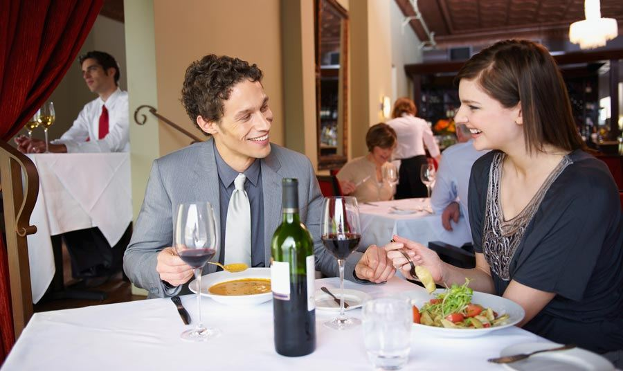 man and woman sitting in front of table