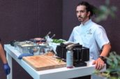 chef behind table with foods
