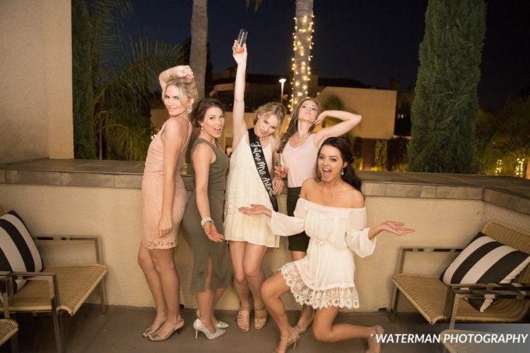 five women standing beside armchair