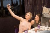 two women sitting beside table while taking selfie
