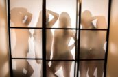 silhouette of women standing near white wall