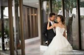 bride and groom standing near glass wall