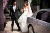 bride and groom holding hands standing near gray sedan