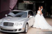 bridge and groom standing beside silver car ]