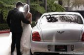 bride and groom standing beside car