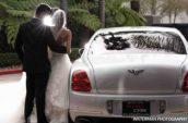 bride and groom standing beside car