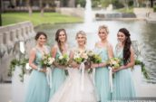 bride and bridesmaids standing near body of water