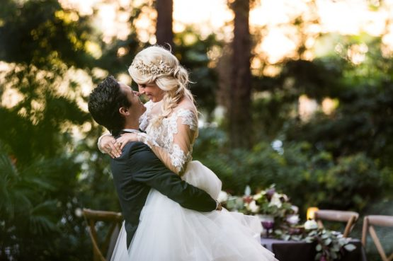 a groom holding up his bride with their noses touching in outdoor setting