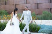 bride and groom holding each other hands walking near yellow-petaled flowers