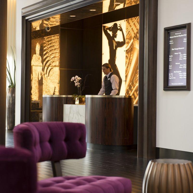 purple suede sofa set near hotel front desk