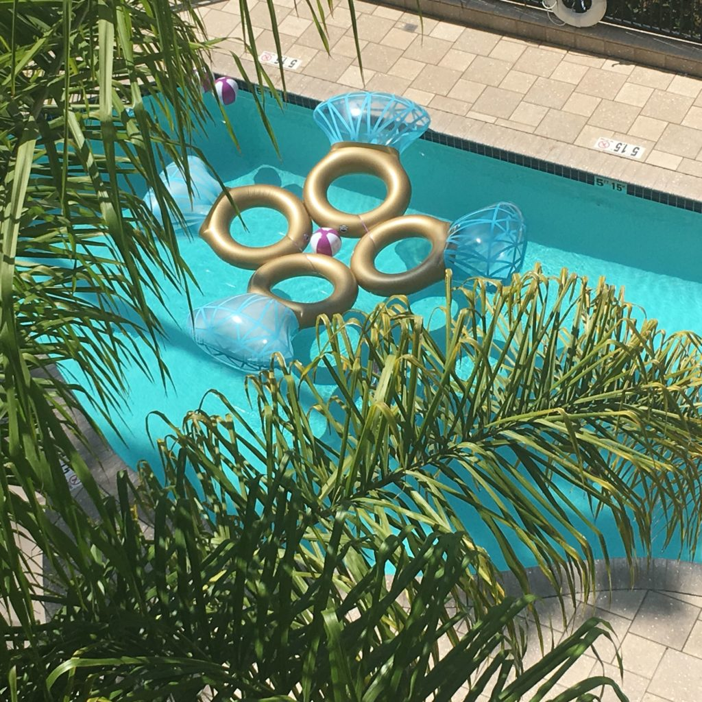 overhead photo of green palm trees and pool