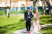 groom and bride walking pathway during daytime