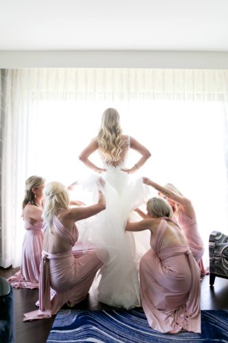 four women lifting the gown of bride