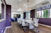 a bright boardroom with a long table and swivel chairs around it