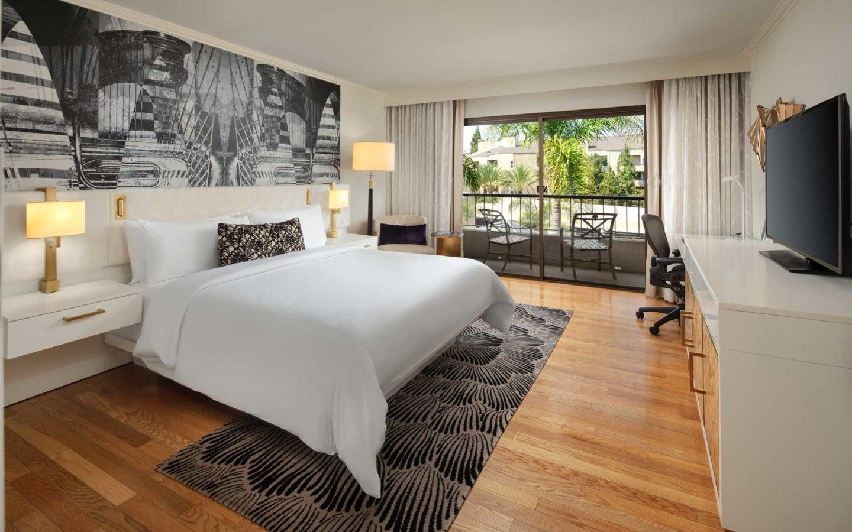 modern luxury hotel room with hardwood floors king bed tv desk and balcony