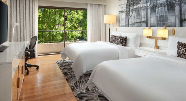 modern luxury hotel room with two queen beds a tv desk and balcony