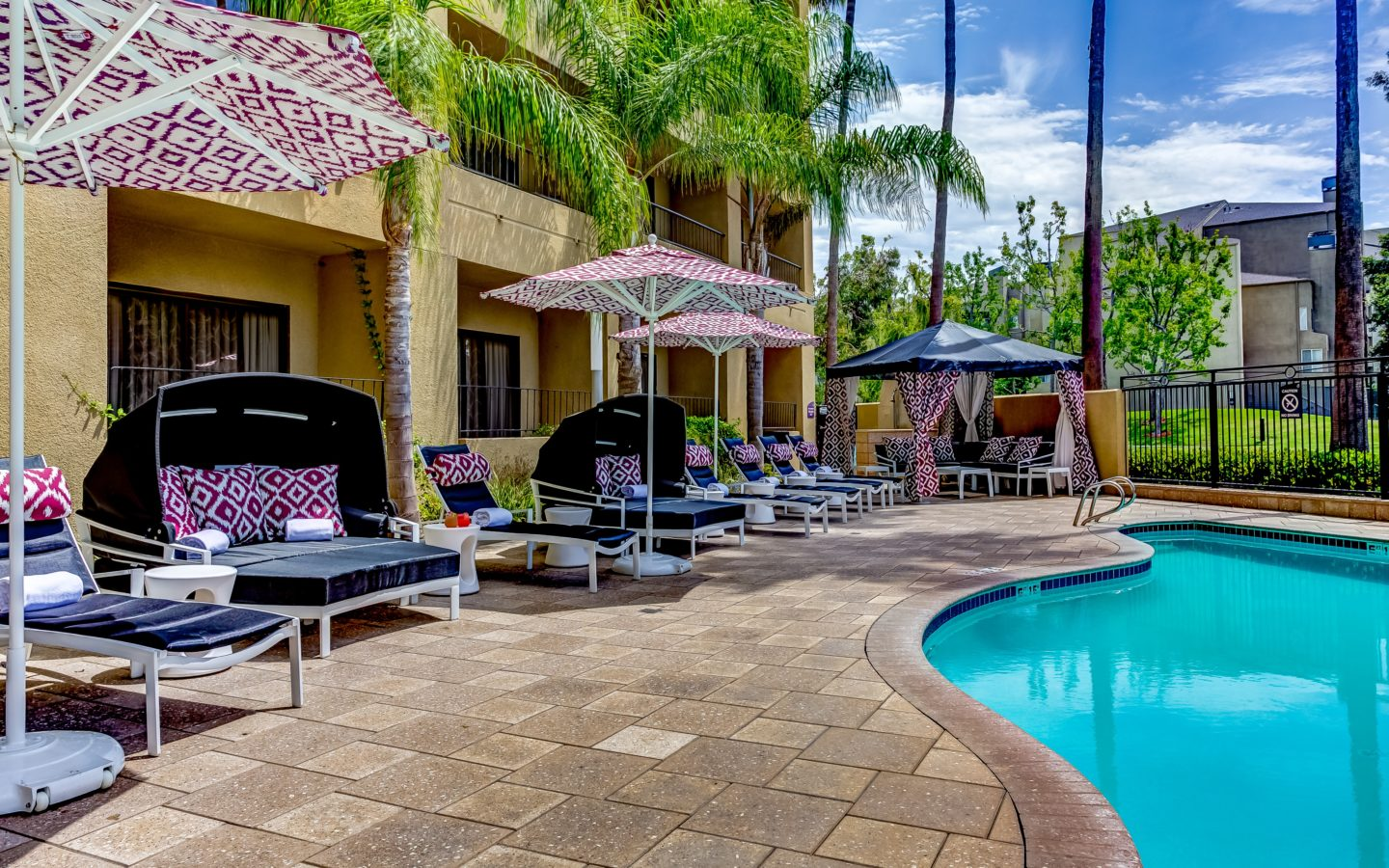 lounge chairs with umbrellas beside pool