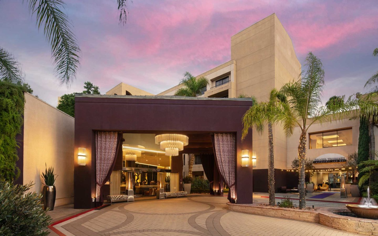 exterior front entrance of beige luxury hotel at sunset surrounded by palm trees