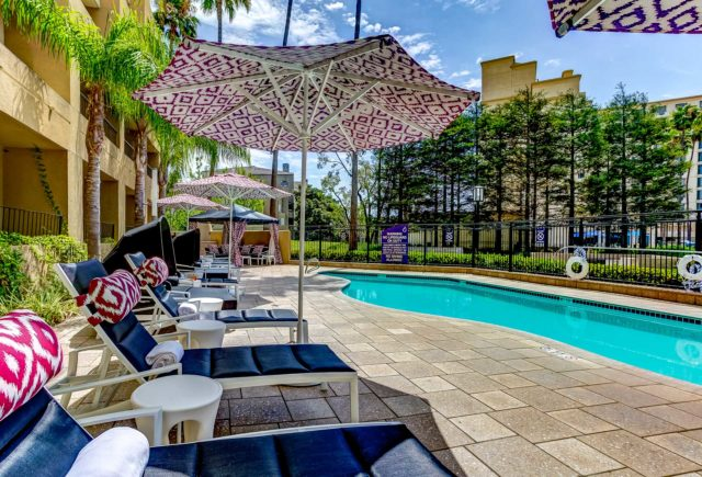 luxury hotel pool lined with chairs and umbrellas