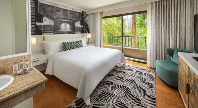 Room with balcony, large bed and black and white rug