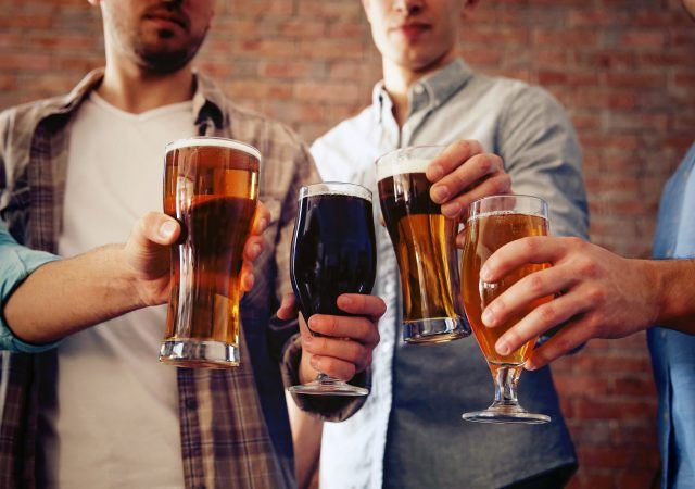 group of men cheers to drinking beer at cascade barrel house