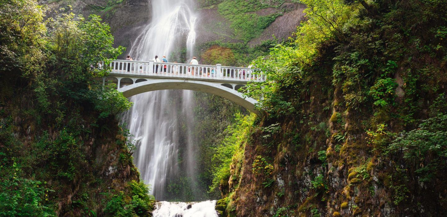 people stand on a bridge overlooking multnomah falls