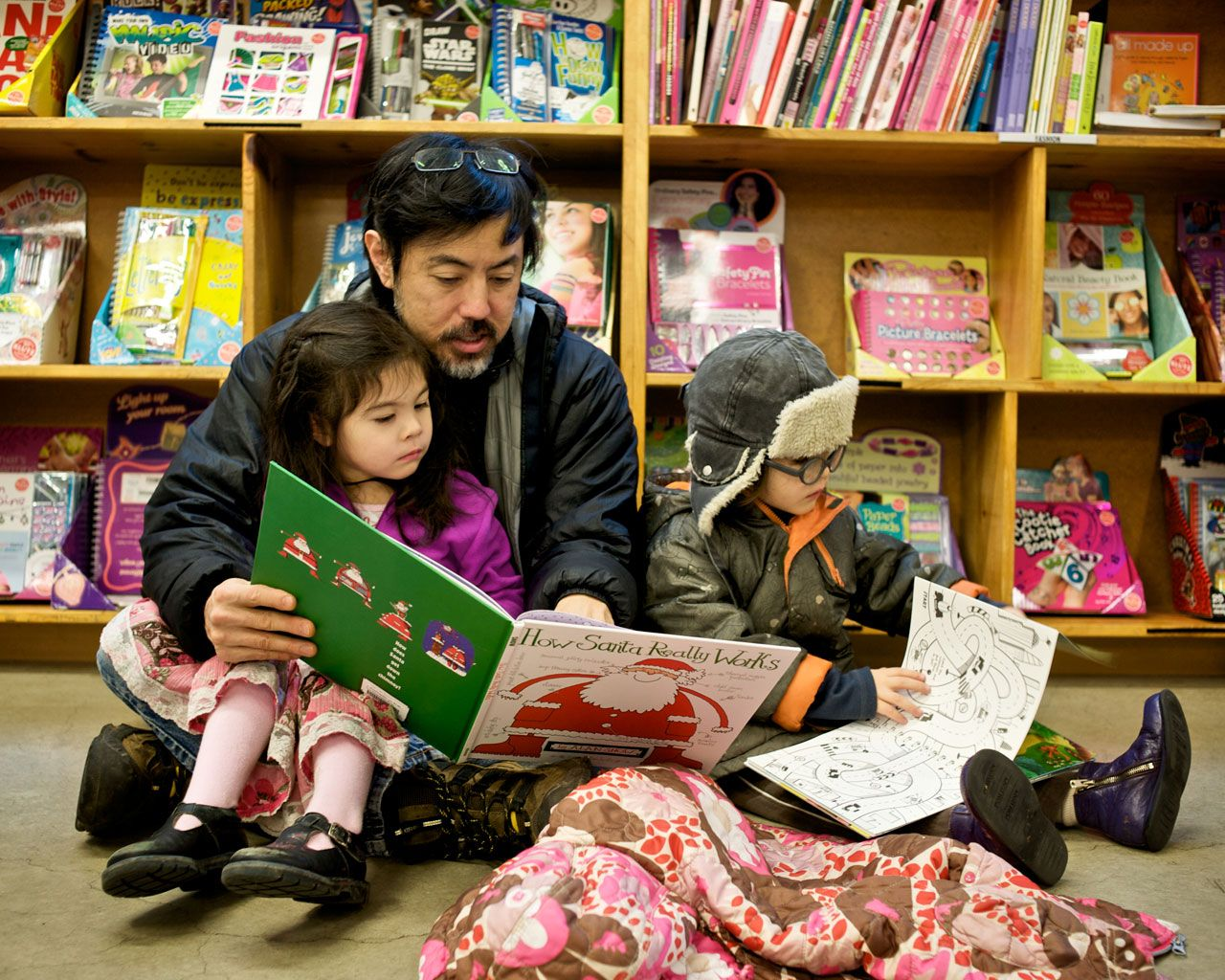 father reads to his children at powells books in portland