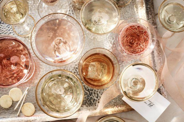 Pink coloured wine and champagne glasses on silver tray