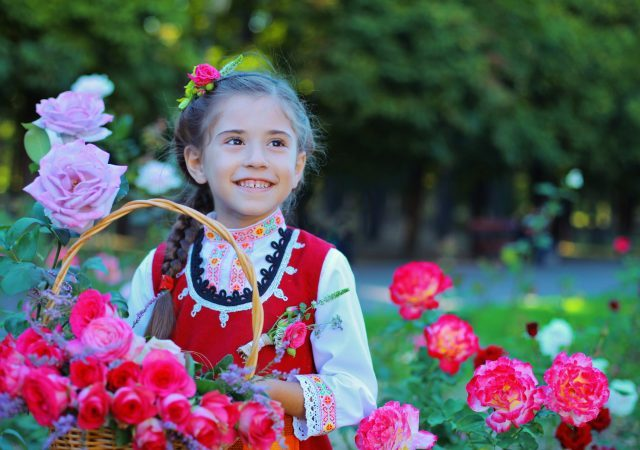 little girls smiling with a basket of roses at the portland rose festival