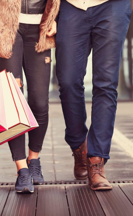 a couple shopping in the city with shopping bags with fall wardrobe