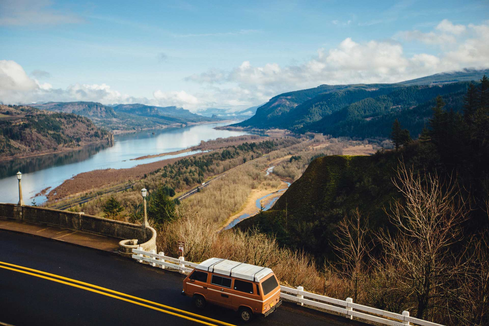 orange vintage camper van driving a paved highway looking over an open landscape with tree-covered hills and a large river