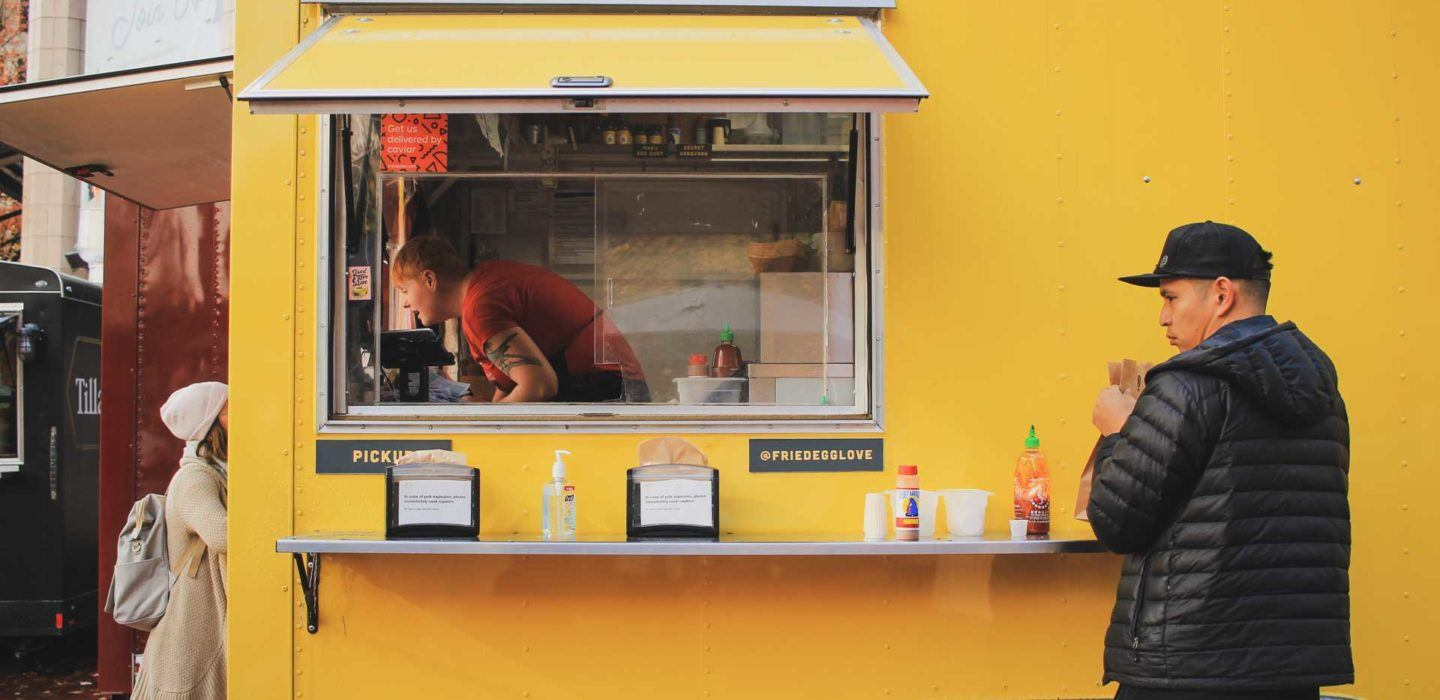 yellow food truck with customers