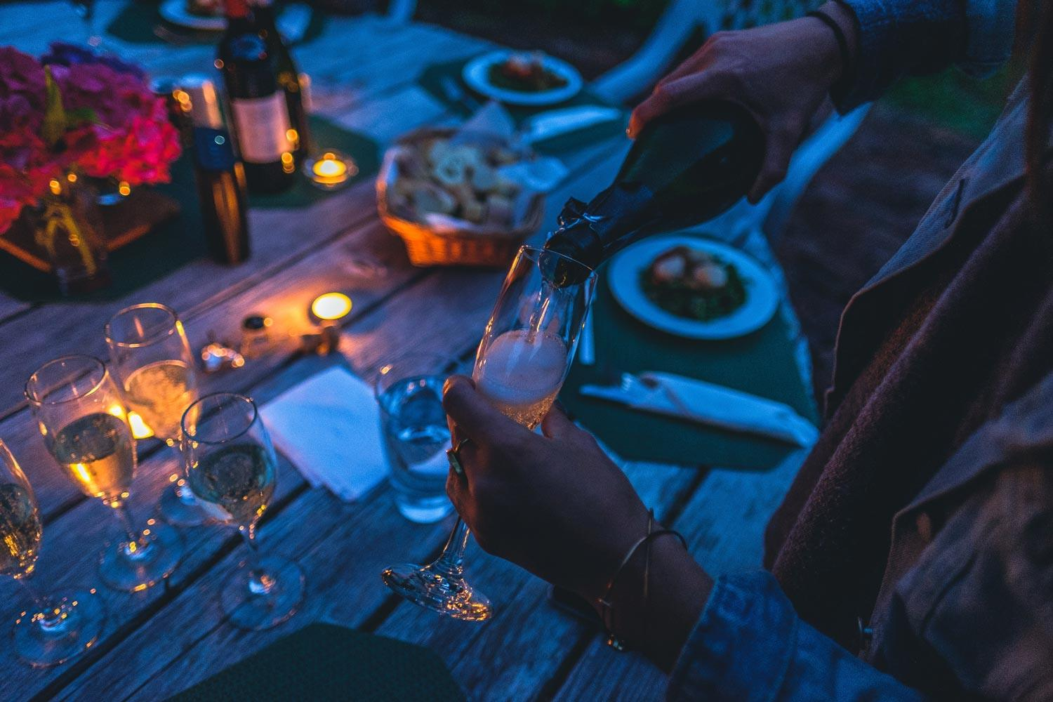woman pouring glass on champagne white dining at outdoor wooden table with tea lights