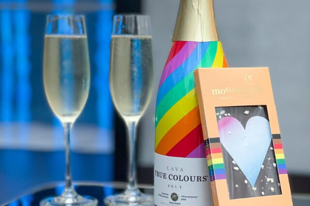 champagne bottle with two full glasses and a chocolate bar