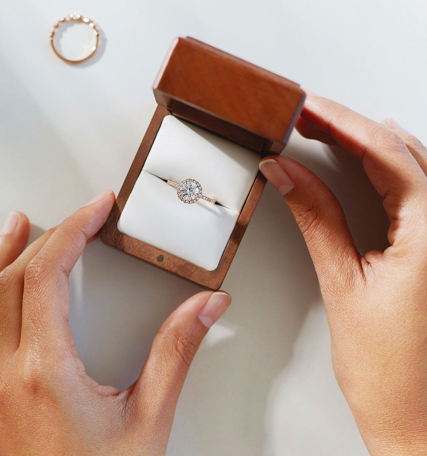 woman's hands holding open a jewelry box containing a diamond ring