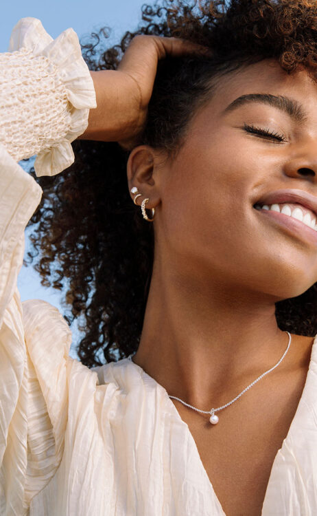 smiling woman lifting hair to reveal three earrings and wearing a necklace boasting a single pearl