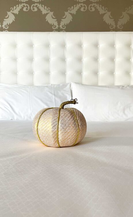 gold pumpkin on top of white bed