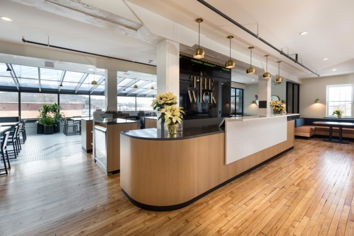 modern hotel lobby with hardwood floors and bright dining area in the background