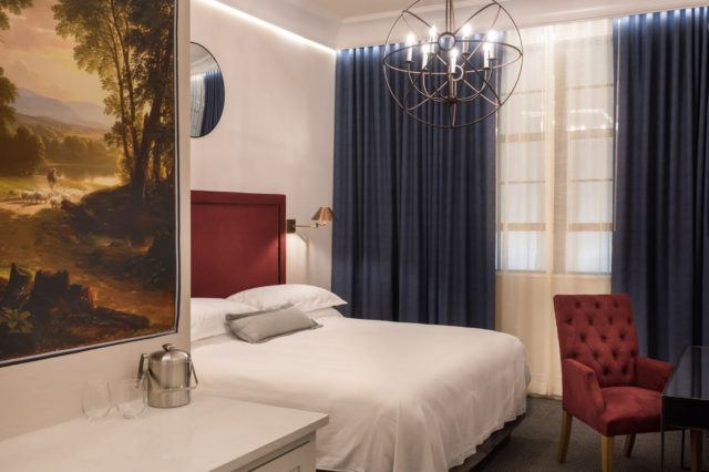 modern luxury hotel room with spherical lighting fixture red chair and large painting