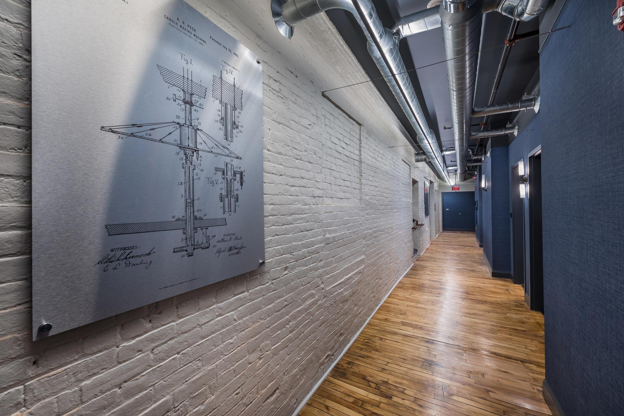 hallway with hardwood floors white brick wall on the left blue wall on the right and schematic drawing hanging