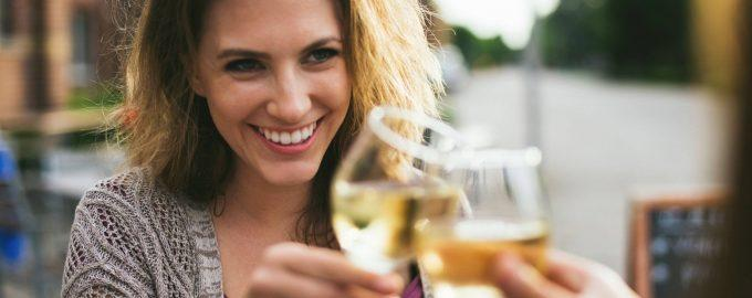 smiling young woman holding glass of white wine saying cheers with her friend