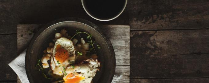 top down view of coffee mug and breakfast dish with eggs served on wooden table