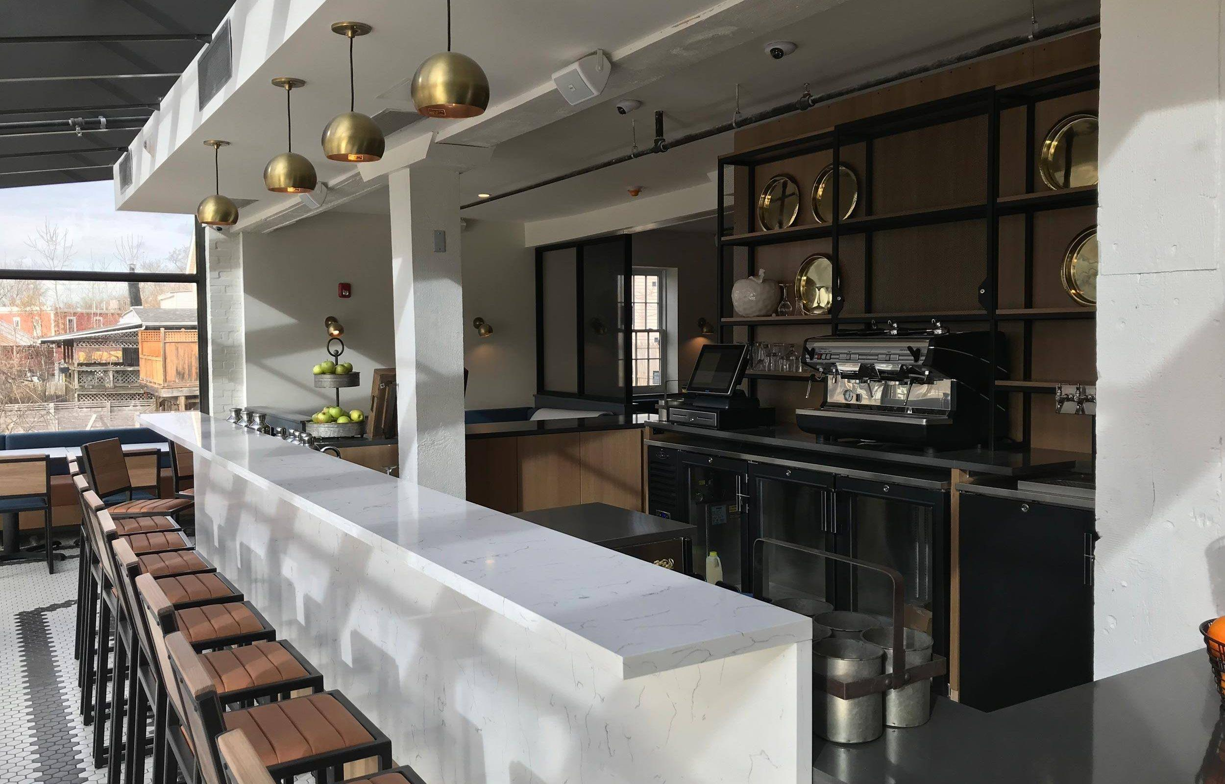 hotel lobby bar with white counter and line of wood stools