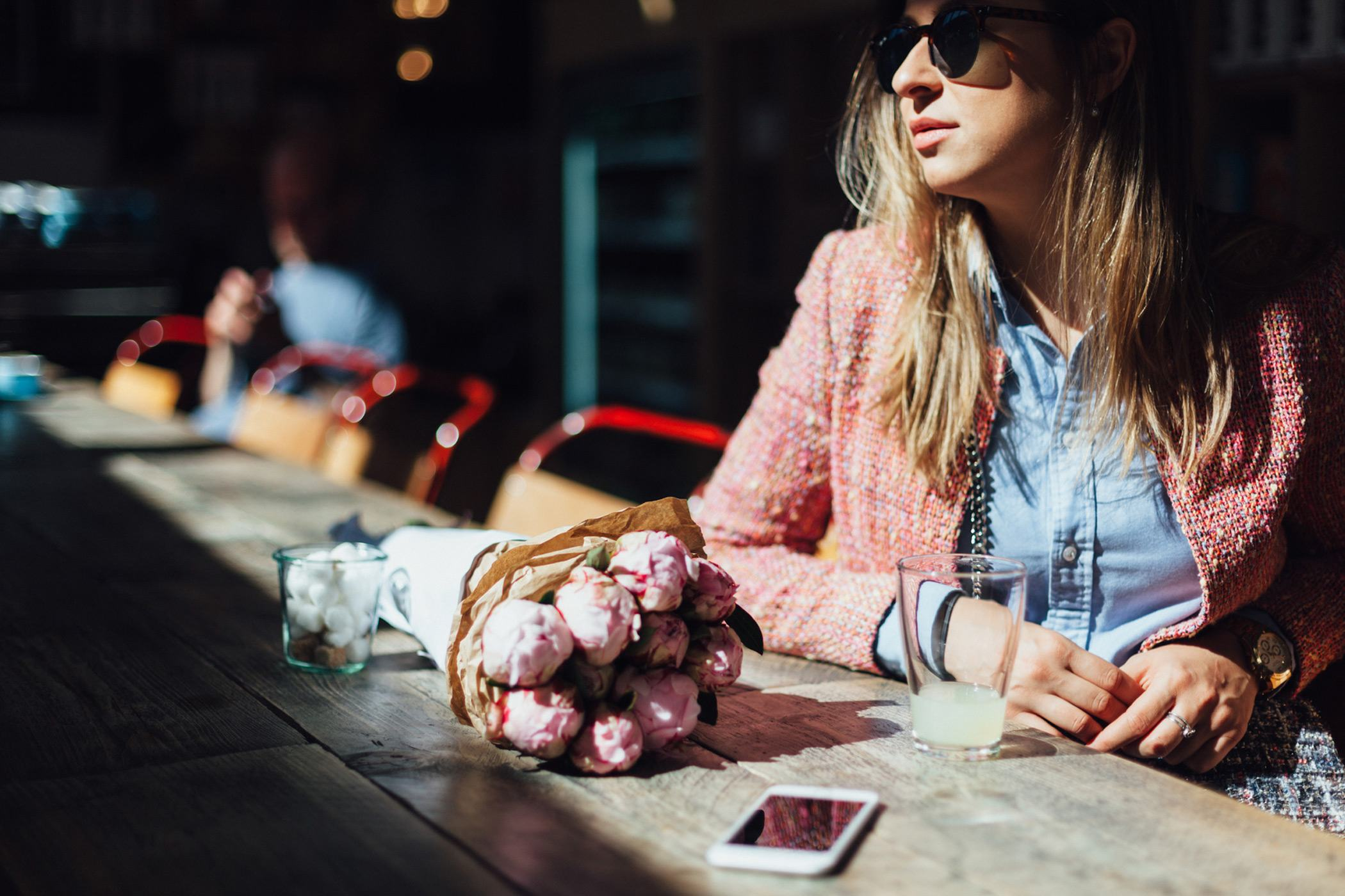 woman wearing sunglasses pink sweater and blue shirt sitting at wooden table with flower bouquet and phone