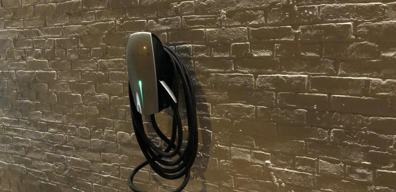 tesla plug vehicle charging station on brick wall