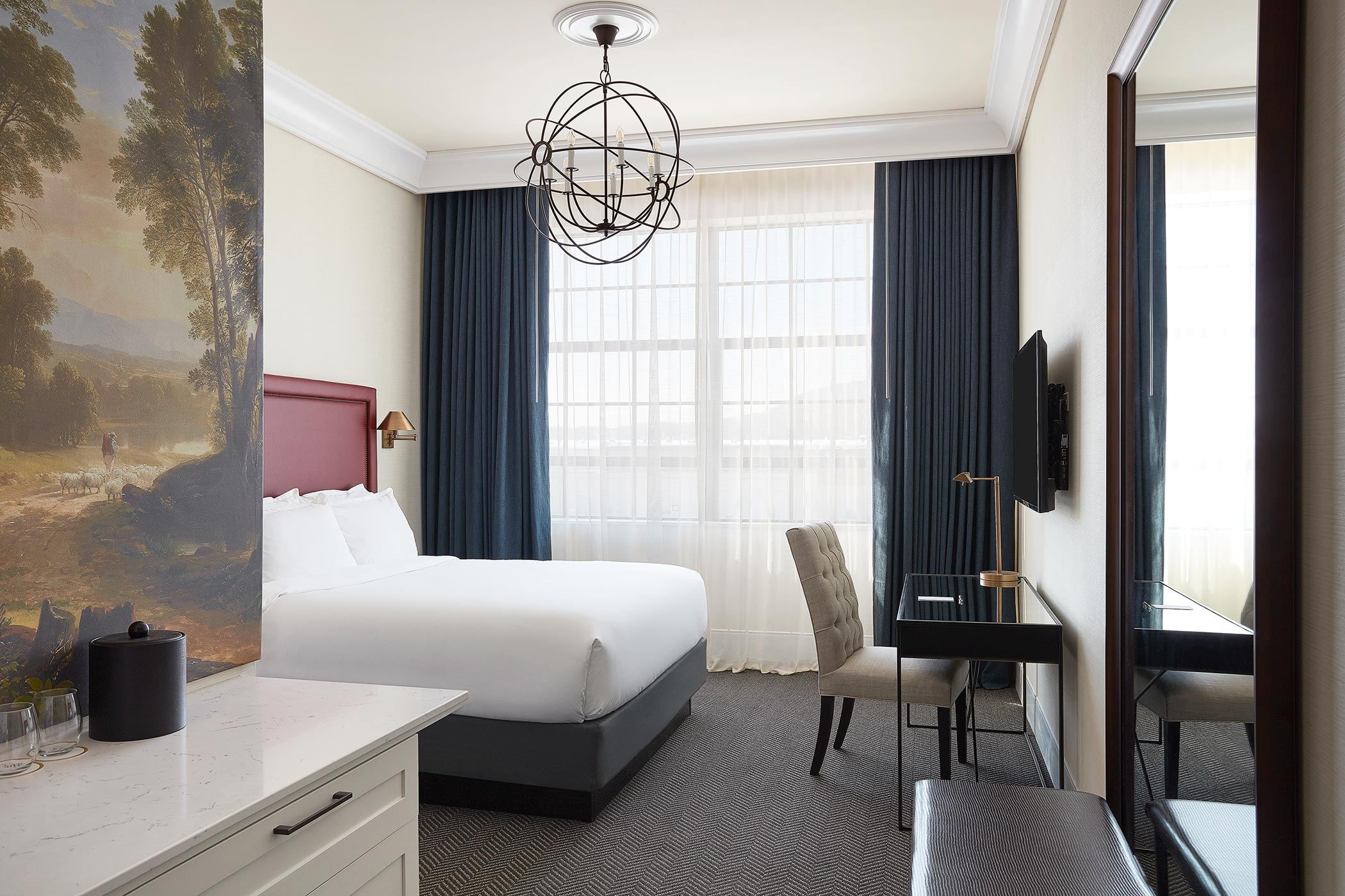 modern luxury hotel room with king bed and large painting