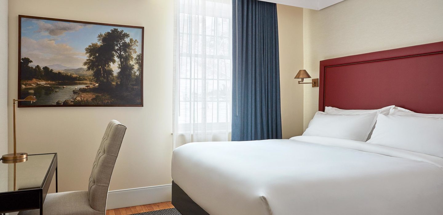 hotel room with painting desk and bed with red backboard